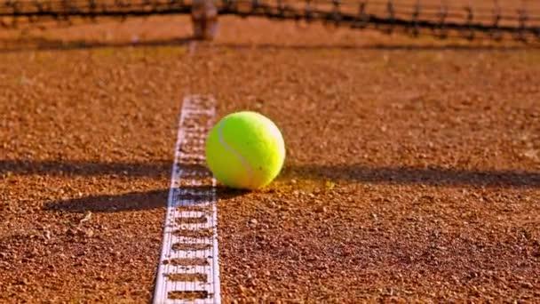Dolly tenisák poblíž řádku na červené tenisový kurt