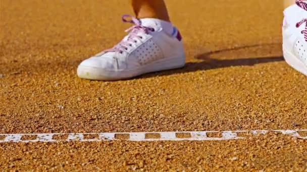 Tenista skákací tenisák na červené tenisový kurt před podáváním