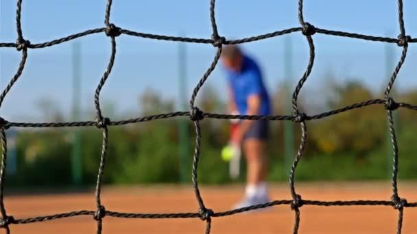 Tenista Slouží tenisový míč s tenisové rakety na Clay Court, síť zepředu, dolly