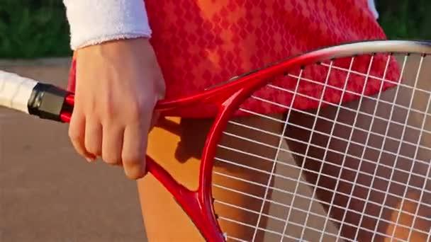 Zblízka tenisový hráč nohou a rukou s tenisovou raketu