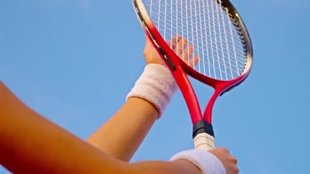 Detailní záběr ruky tenisový hráč udeří net její tenisové rakety proti modré obloze