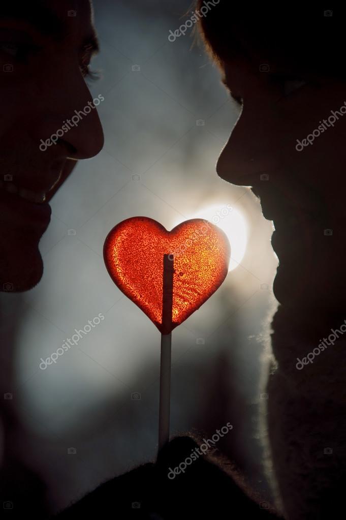 Couple silhouette in love hold heart shape lollipop