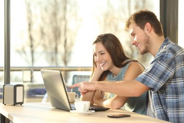 Couple searching information in a laptop