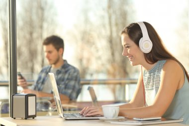 Woman with headphones typing in a laptop