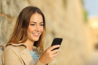 Happy woman using a smart phone in an old town