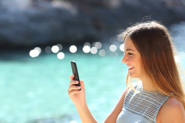Woman using a smart phone in a tropical beach in vacations