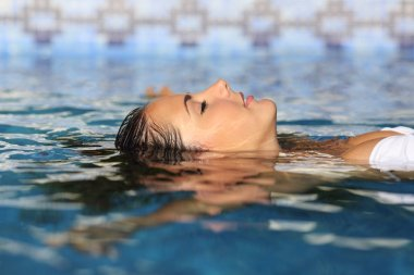 Profile of a beauty relaxed woman face floating in water