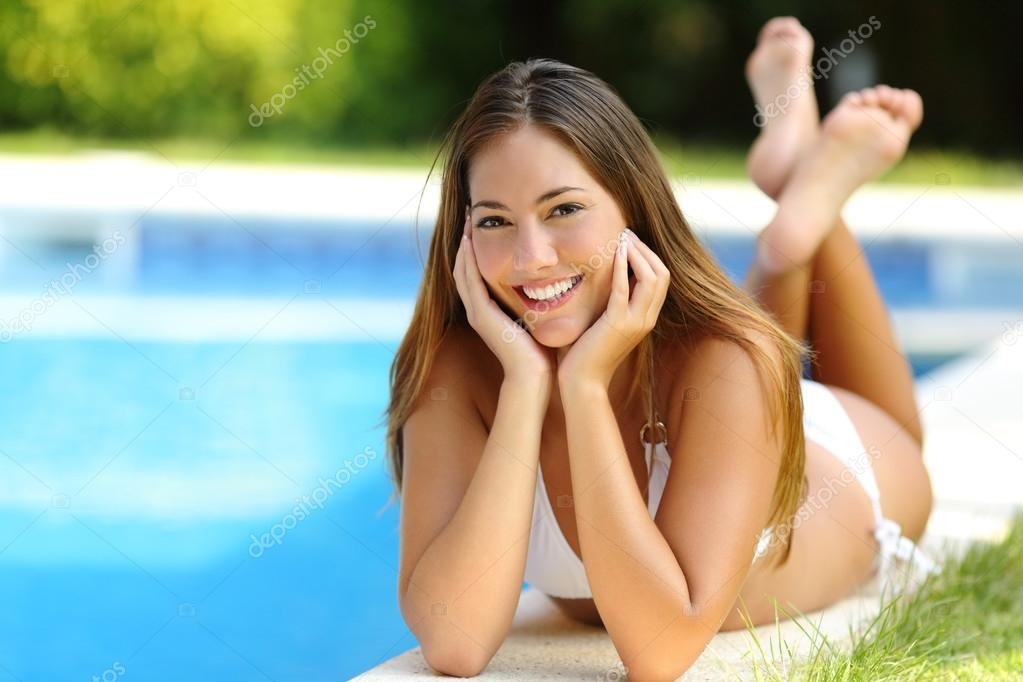 Happy girl posing wearing bikini on a pool side in summer vacations