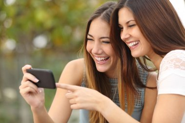 Two funny women friends laughing and sharing media in a smart phone