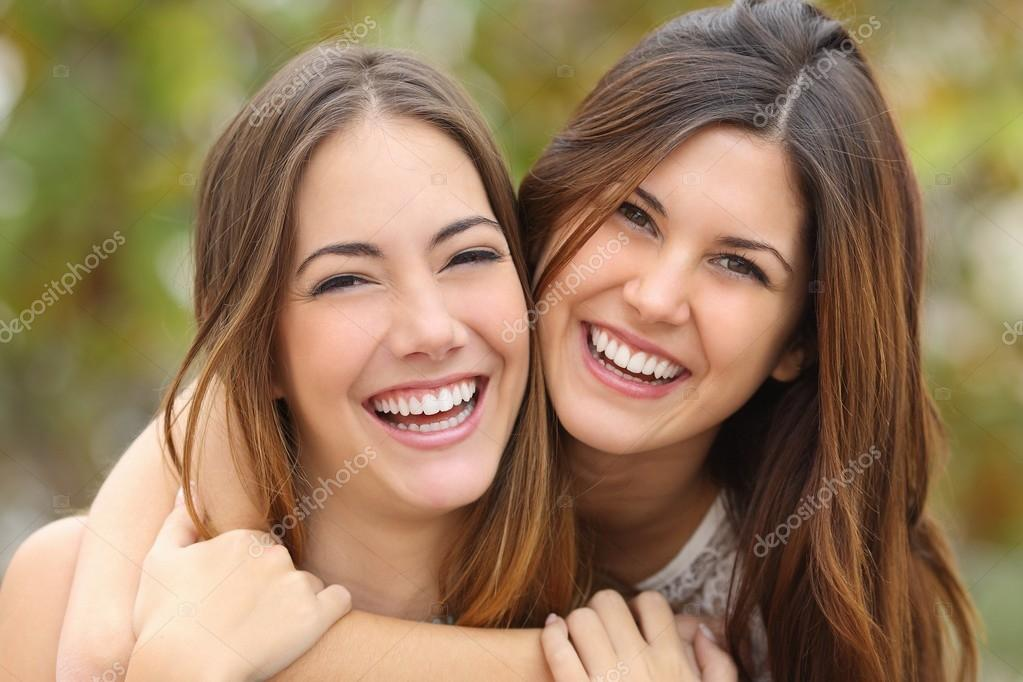 Two women friends laughing with a perfect white teeth