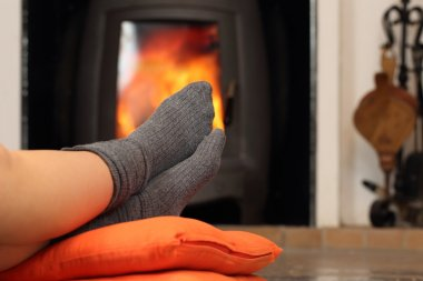 Woman feet with socks resting near fire place