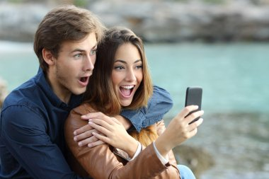 Shocked couple watching a smart phone on holidays