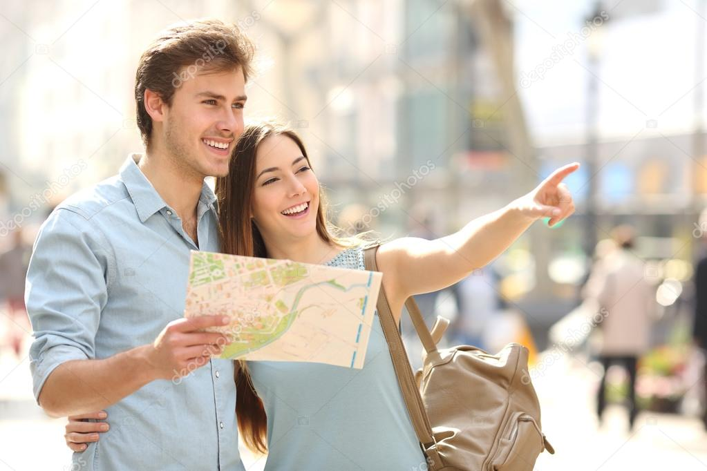 Couple of tourists consulting a city guide searching locations