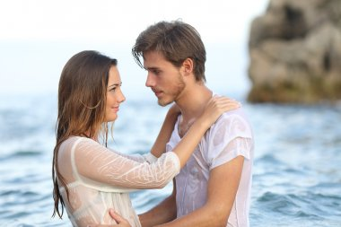 Young couple in love looking each other bathing in the sea