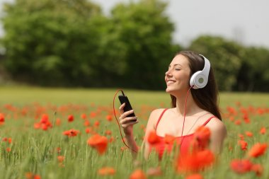 Woman breathing and listening music in a field
