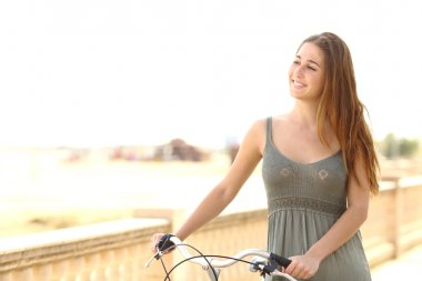 Healthy teen girl walking with a bike in summer