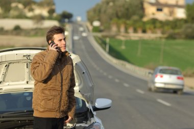 Happy man calling roadside assistance for his breakdown car