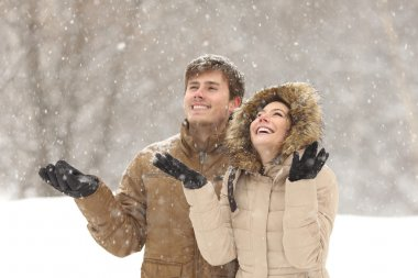 Funny couple watching snow in winter