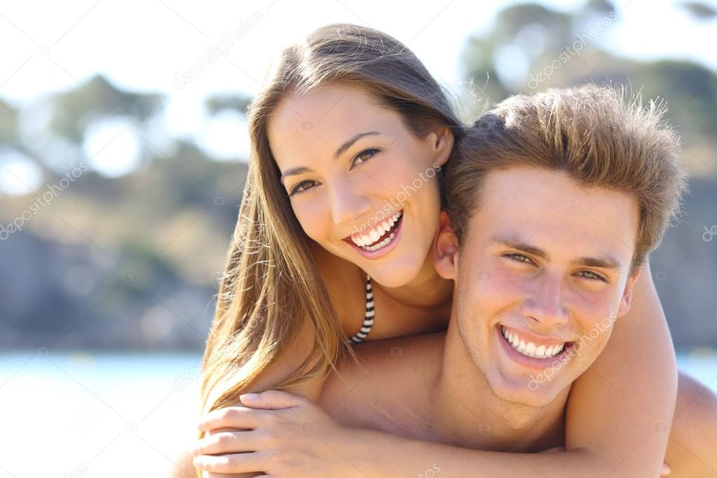 Happy couple with perfect smile and white teeth posing on the beach looking at camera