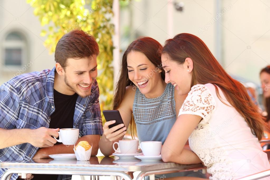 Friends watching media in a smart phone in a coffee shop