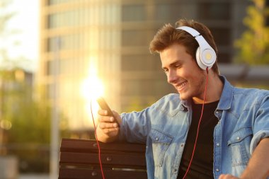 Happy man listening to music from a smart phone