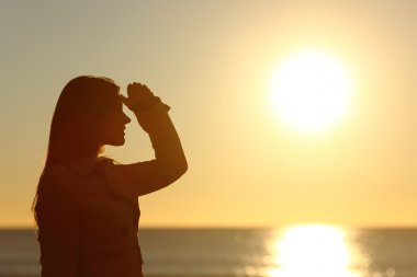 Silhouette of a woman looking forward at sunset
