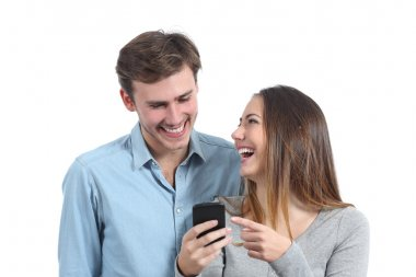 Happy friends laughing and watching a smart phone