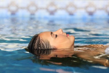Woman face relaxing floating on water of a pool or spa