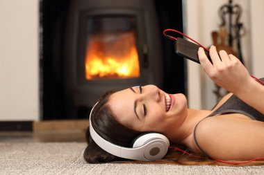 Woman listening to the music from a smartphone at home