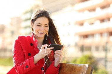Woman watching videos in a smart phone with earphones