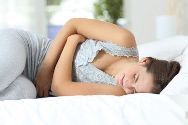 Girl suffering menstrual pains on the bed