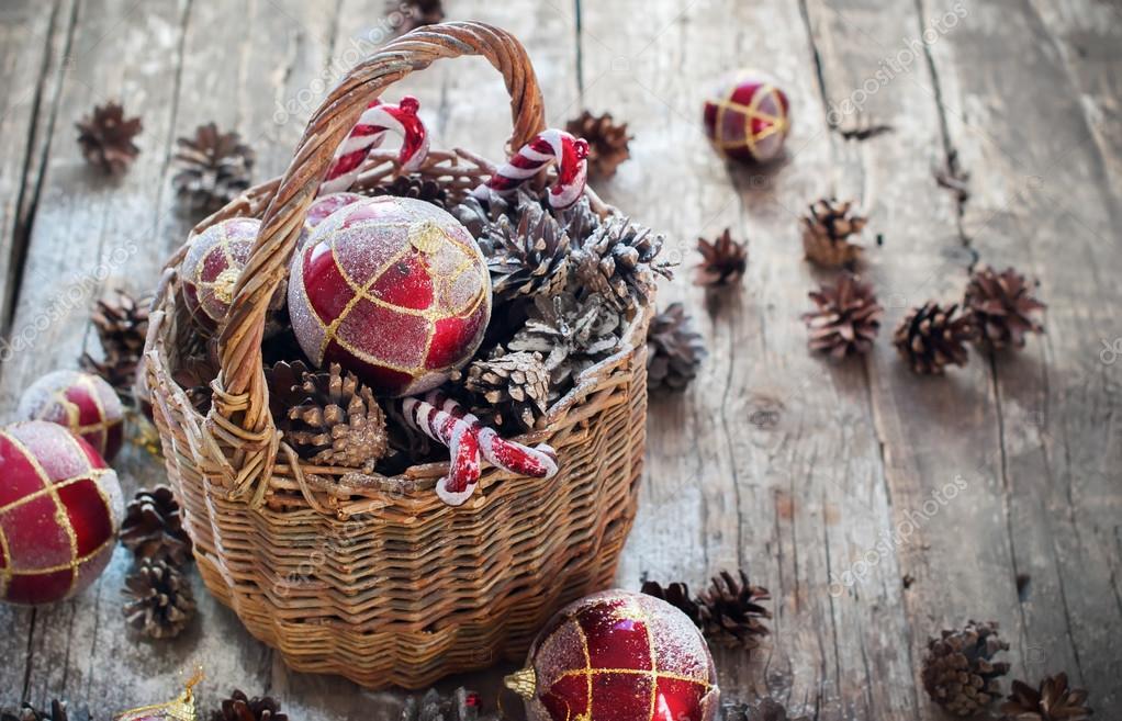 Weinlese-Weihnachtsgeschenke im Korb, Rote Kugeln, Tannenzapfen ...