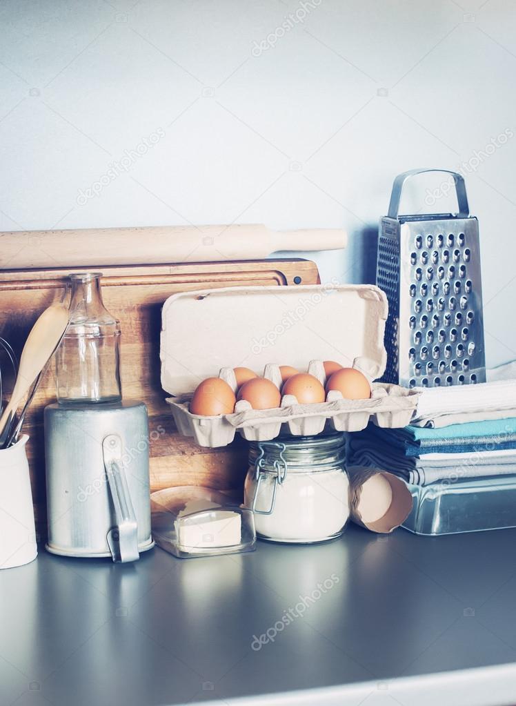 Uova, stoviglie, alimentari, cose diverse sul tavolo di cucina ...