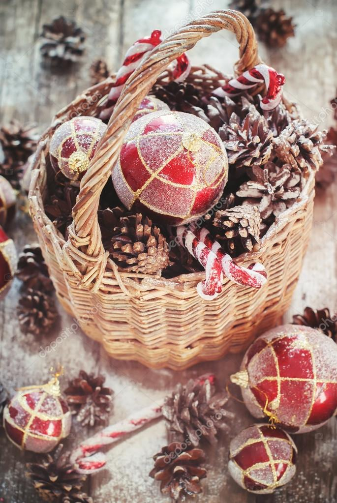 Weinlese-Weihnachtsgeschenke im ländlichen Korb. Rote Kugeln, süße ...