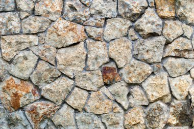 Masonry Wall of color stones with irregular pattern, background