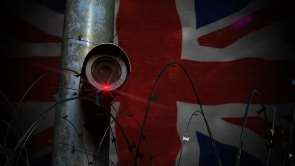 Security camera on pole with razor wire and United Kingdom flag