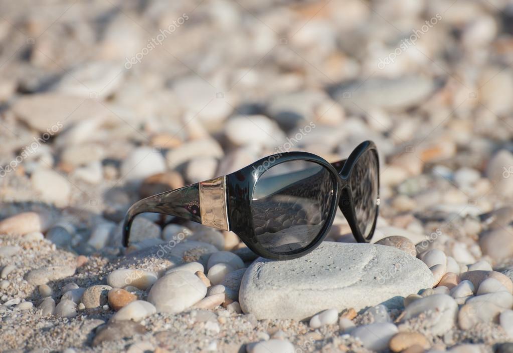 Zonnebril op het strand met kiezels u stockfoto nata