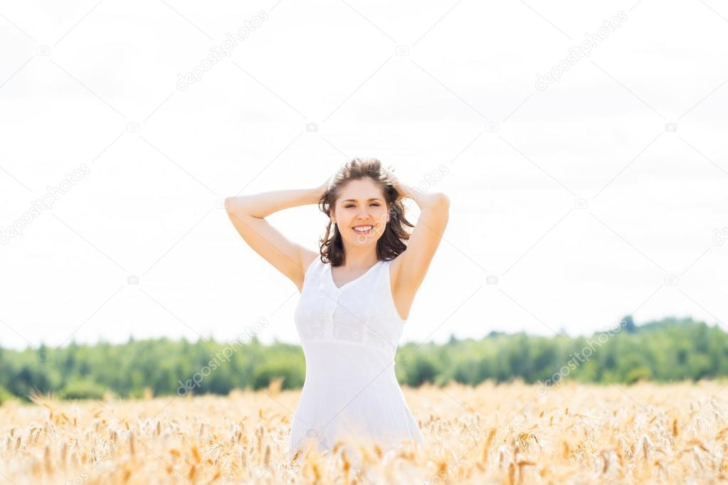 Young and happy woman in a meadow of rye