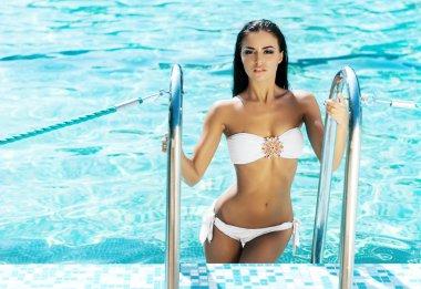 Young and sexy woman in a white bikini in the swimming pool