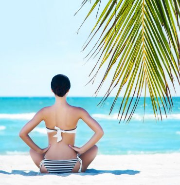 Back of a young woman relaxing on a tropical beach