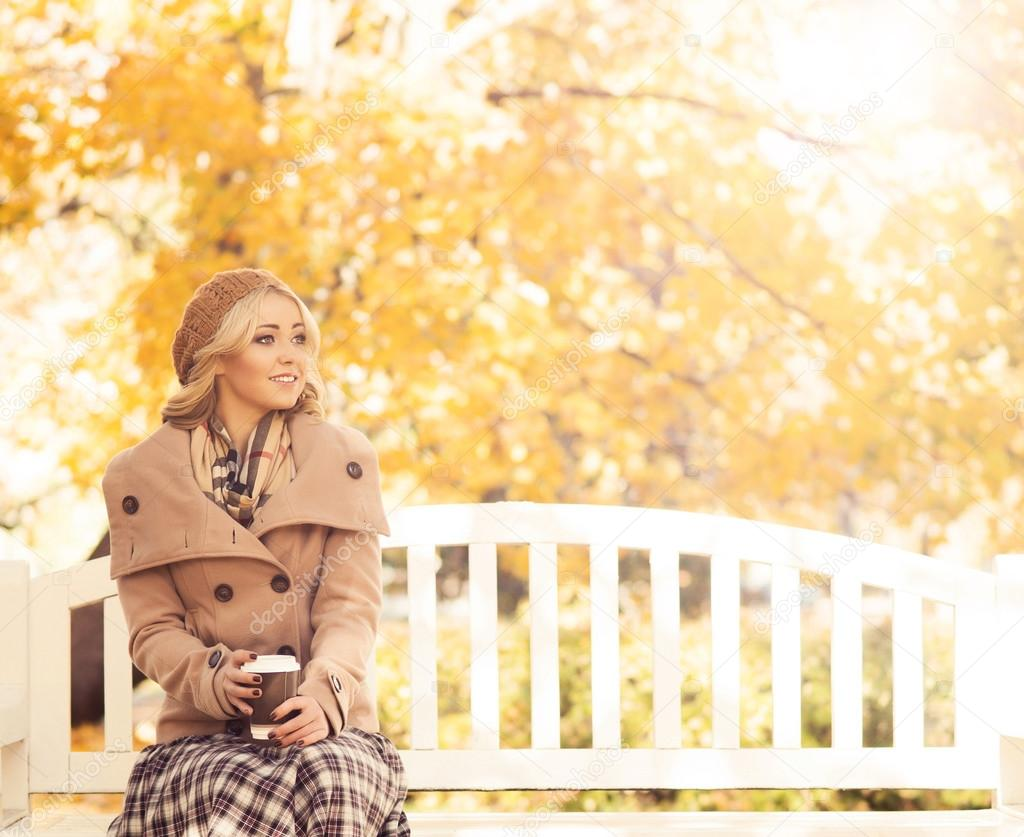 Young and attractive girl sitting on a bench in an autumn park