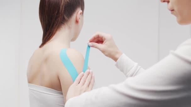 A terapeuta kinesio szalagot használ a női testen. Fizioterápia, kineziológia és gyógyulási kezelés.