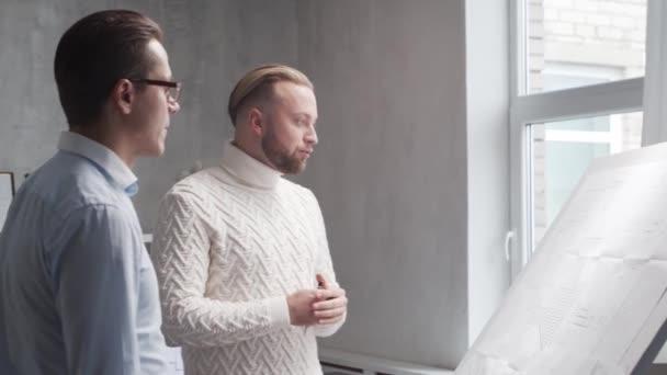 Architekt a jeho kolega pracují v podkroví pomocí kreslicí tabule. Pracoviště mladého inženýra v moderní kanceláři. Koncept developmentu nemovitostí.