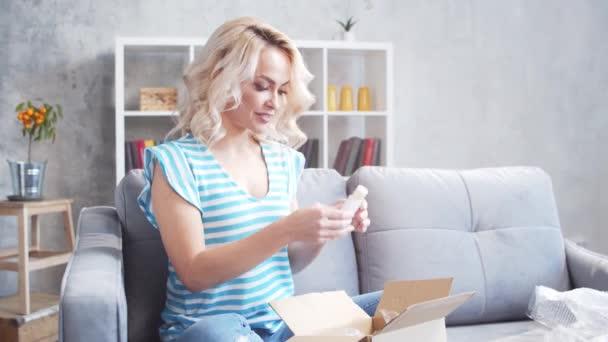 Junge und glückliche Frau beim Auspacken von Paketschachteln auf dem heimischen Sofa sitzend. Lieferkonzept.