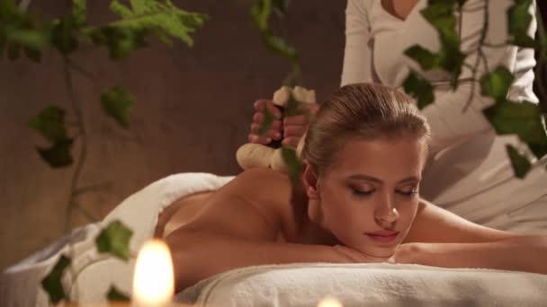Mladá, zdravá a krásná žena dostává v lázeňském salonu masáže bylinnými koulemi. Zdravý životní styl a koncepce péče o tělo.