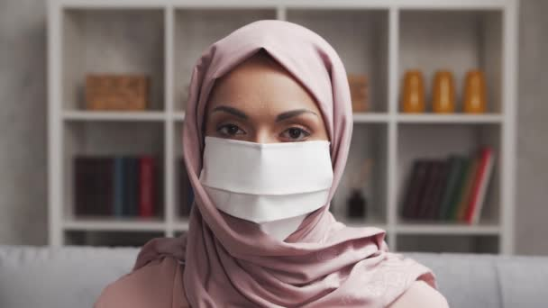 Close-up portrait of young Muslim girl in hijab and protective mask. Sad Middle Eastern woman is sitting in front of the camera. Self-isolation, lockdown and quarantine concepts.