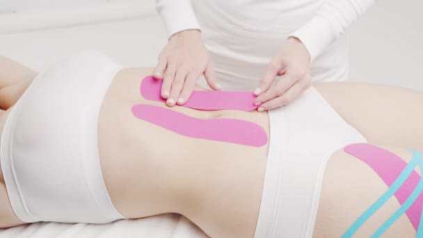 Therapist is applying kinesio tape to female body. Physiotherapy, kinesiology and recovery treatment.