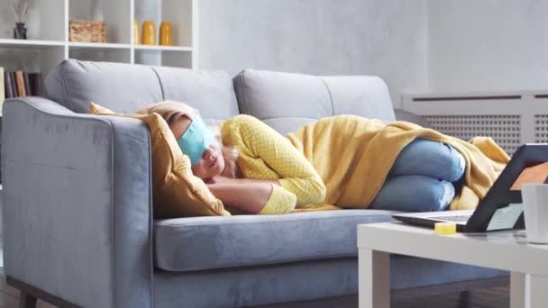 Freelancer Mädchen müde von der Arbeit schläft auf der Couch am Morgen. Die junge Frau schlief ein, während sie zu Hause arbeitete. Lockdown und Remote Job Konzepte.