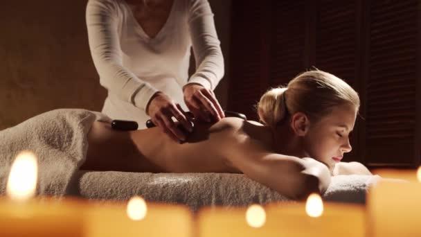 Mladá, zdravá a krásná žena dostává masážní terapii horkými kameny v lázeňském salonu. Zdravý životní styl a koncepce péče o tělo.
