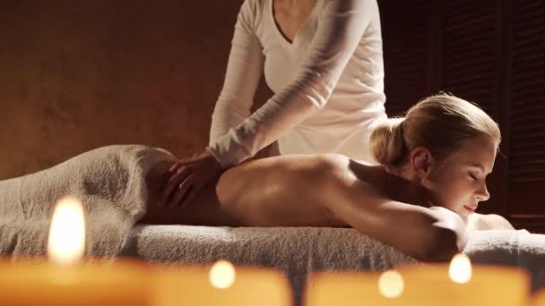 Junge, gesunde und schöne Frau bekommt Hot-Stone-Massage-Therapie im Wellness-Salon. Gesunder Lebensstil und Körperpflegekonzept.